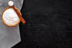 Food helps digestion. Greek yogurt in brown bowl near spoon on blue tablecloth, black background top view copy space. Food helps digestion. Greek yogurt in brown stock photos