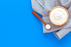 Food helps digestion. Greek yogurt in brown bowl near spoon on blue tablecloth, blue background top view copy space. Food helps digestion. Greek yogurt in brown royalty free stock photo