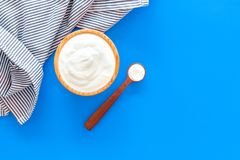 Food helps digestion. Greek yogurt in brown bowl near spoon on blue tablecloth, blue background top view copy space. Food helps digestion. Greek yogurt in brown stock photography