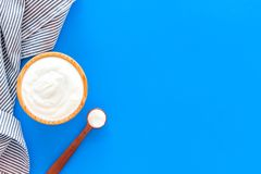 Food helps digestion. Greek yogurt in brown bowl near spoon on blue tablecloth, blue background top view copy space. Food helps digestion. Greek yogurt in brown royalty free stock images