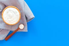 Food helps digestion. Greek yogurt in brown bowl near spoon on blue tablecloth, blue background top view copy space. Food helps digestion. Greek yogurt in brown stock photo