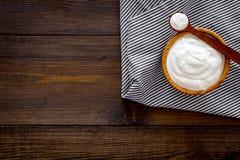 Food helps digestion. Greek yogurt in brown bowl near spoon on blue tablecloth, dark wooden background top view copy. Food helps digestion. Greek yogurt in brown stock photo