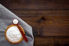 Food helps digestion. Greek yogurt in brown bowl near spoon on blue tablecloth, dark wooden background top view copy. Food helps digestion. Greek yogurt in brown stock photography
