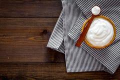 Food helps digestion. Greek yogurt in brown bowl near spoon on blue tablecloth, dark wooden background top view copy. Food helps digestion. Greek yogurt in brown stock image