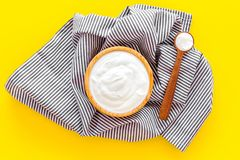 Food helps digestion. Greek yogurt in brown bowl near spoon on blue tablecloth, yellow background top view.  royalty free stock photos