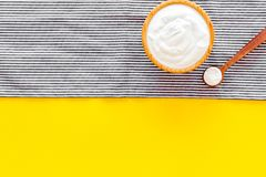 Food helps digestion. Greek yogurt in brown bowl near spoon on blue tablecloth, yellow background top view copy space. Food helps digestion. Greek yogurt in royalty free stock photography