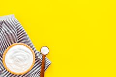 Food helps digestion. Greek yogurt in brown bowl near spoon on blue tablecloth, yellow background top view copy space. Food helps digestion. Greek yogurt in stock image