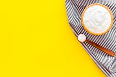 Food helps digestion. Greek yogurt in brown bowl near spoon on blue tablecloth, yellow background top view copy space. Food helps digestion. Greek yogurt in stock photos