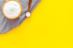 Food helps digestion. Greek yogurt in brown bowl near spoon on blue tablecloth, yellow background top view copy space. Food helps digestion. Greek yogurt in stock images