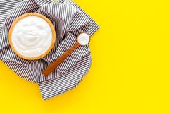 Food helps digestion. Greek yogurt in brown bowl near spoon on blue tablecloth, yellow background top view copy space. Food helps digestion. Greek yogurt in royalty free stock photo