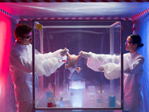 Food helth check. Two scientists, a men and a woman, conducting chemical experiments on a raw chicken in a protection enclosure, in a containment tent Royalty Free Stock Photography