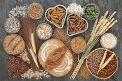 Food High in Dietary Fiber. Food high in dietary fibre with whole grain bread and seeded rolls, whole wheat pasta, seeds, cereals and grains on marble background stock photography