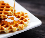 Honey pouring on a fresh waffles Royalty Free Stock Photos