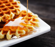 Honey pouring on a fresh waffles Royalty Free Stock Images