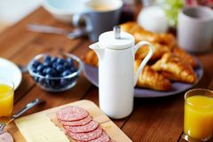 Coffee pot and food on served table at breakfast Royalty Free Stock Images