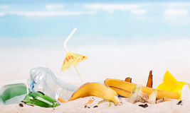 Food and household waste in sand against the blue sea. Royalty Free Stock Image
