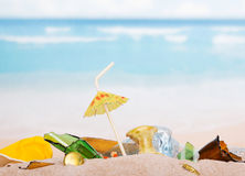 Food and household waste in the sand against  sea. Royalty Free Stock Photo