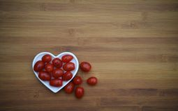 Food image of ripe red plum tomatoes and one has a drawn on smile and placed with a white love heart shape dish. A rustic food image with dark wood background of Royalty Free Stock Photo