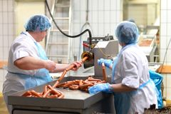 Food industry: workers in the production of original German brat. Wurst in a large butcher`s shop Stock Photography
