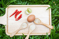 Food ingredients for cooking. Consisted of lime, red chilli, wooden spoon with rice Stock Images