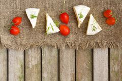 Food ingredients: French cheese and cherry tomatoes on a wooden surface Stock Photography