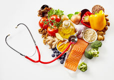 Food ingredients in heart with stethoscope. Different fresh food ingredients in heart shape with stethoscope on white background royalty free stock images
