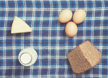 Food ingredients. Hen eggs, bottle of milk, rye bread, cheese on gingham table cloth Royalty Free Stock Photography