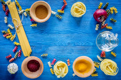 Food ingredients for Italian pasta on blue wooden desk background top view copyspace.  Stock Photos
