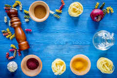 Food ingredients for Italian pasta on blue wooden desk background top view copyspace.  Royalty Free Stock Photo