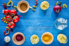 Food ingredients for Italian pasta on blue wooden desk background top view copyspace.  Stock Photo