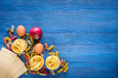 Food ingredients for Italian pasta on blue wooden desk background top view copyspace.  Royalty Free Stock Images