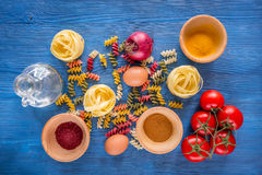 Food ingredients for Italian pasta on blue wooden desk background top view Stock Photo