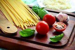 Food ingredients. Italian pasta ingredients including spaghetti, tomato, basil, garlic and cheese Stock Photos