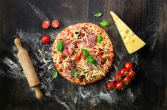 Food ingredients for italian pizza, cherry tomatoes, flour, cheese, basil, rolling pin, spices on dark background. Top. Food ingredients for italian pizza royalty free stock photography