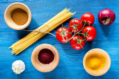 Food ingredients for Italian spaghetti on blue wooden desk background top view Stock Photography
