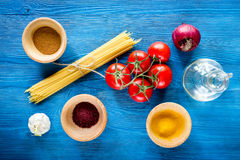Food ingredients for Italian spaghetti on blue wooden desk background top view Stock Image