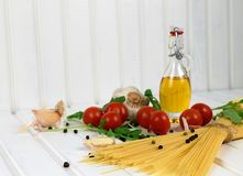 Food ingredients for Italian spaghetti onwhite wooden background. Food ingredients for Italian spaghetti on white wooden background with much copy space of your Royalty Free Stock Images