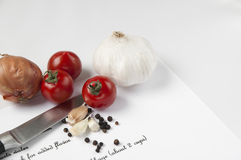 Food ingredients, knife and recipe. Onion, tomatoes, garlic, peppercorns and a knife on a paper with recipe Royalty Free Stock Photos