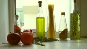 Food ingredients near kitchen window. Cooking oil and kitchen herbs stock video