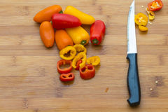 Food Ingredients: Red and Orange Peppers in Cutting Board Royalty Free Stock Photography