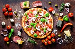 Food ingredients and spices for cooking delicious italian pizza. Mushrooms, tomatoes, cheese, onion, oil, pepper, salt. Basil, grater, olive on rustic stock photos