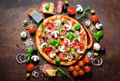 Food ingredients and spices for cooking delicious italian pizza. Mushrooms, tomatoes, cheese, onion, oil, pepper, salt. Basil, grater, olive on rustic royalty free stock photos