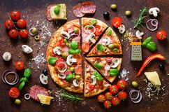 Food ingredients and spices for cooking delicious italian pizza. Mushrooms, tomatoes, cheese, onion, oil, pepper, salt. Basil, grater, olive on rustic Stock Image