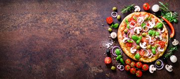 Food ingredients and spices for cooking delicious italian pizza. Mushrooms, tomatoes, cheese, onion, oil, pepper, salt. Basil, olive on rustic background Stock Images