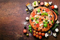 Food ingredients and spices for cooking delicious italian pizza. Mushrooms, tomatoes, cheese, onion, oil, pepper, salt. Basil, olive on rustic background Royalty Free Stock Images