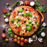 Food ingredients and spices for cooking mushrooms, tomatoes, cheese, onion, oil, pepper, salt, basil, grater, olive and. Delicious italian pizza on rustic royalty free stock image