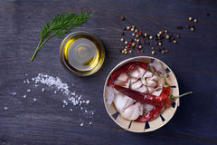 Food ingredients: spices, herbs, garlic, pepper mix, chili pepper, olive oil, dill. Top view on rustic wooden table. Stock Photos