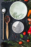 Food ingredients: spices, salt, vegetebles, herbs, spoons and plates royalty free stock images