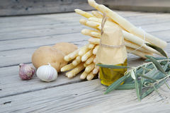 Food ingredients on a wooden surface. Food ingredients for preparing asparagus with potatoes.Wooden surface Stock Images