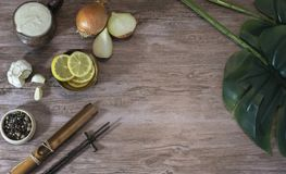 Food ingredients on a wooden table with plant leaves stock image